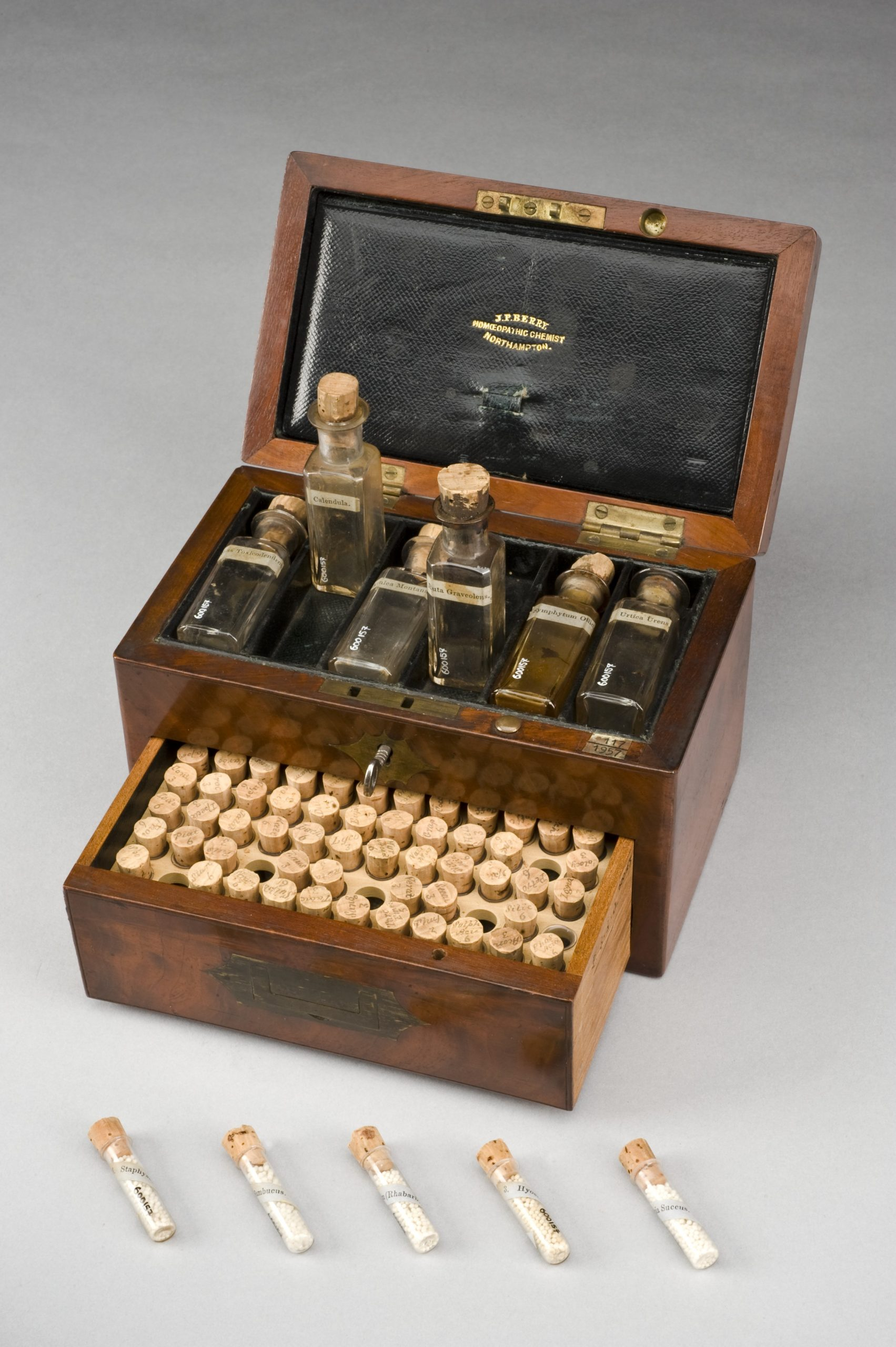 """L0057796 Homeopathic medicine chest, Northamptonshire, England, 1801- Credit: Science Museum, London. Wellcome Images images@wellcome.ac.uk http://wellcomeimages.org This mahogany medicine chest contains 69 small glass vials with handwritten labels and six large bottles. Homeopathy relies on the idea that 'like cures like'. For instance, if you are vomiting, your treatment will be something that causes vomiting but in a smaller, much diluted dose. One of the large bottles is labelled """"Urtica urens"""". This treatment is made from a dwarf stinging nettle and is used on burns and skin irritations, the same effect the plant has on the body.  maker: Berry, J P  Place made: Northampton, Northamptonshire, England, United Kingdom made: 1801-1900 Published:  -   Copyrighted work available under Creative Commons Attribution only licence CC BY 4.0 http://creativecommons.org/licenses/by/4.0/"""